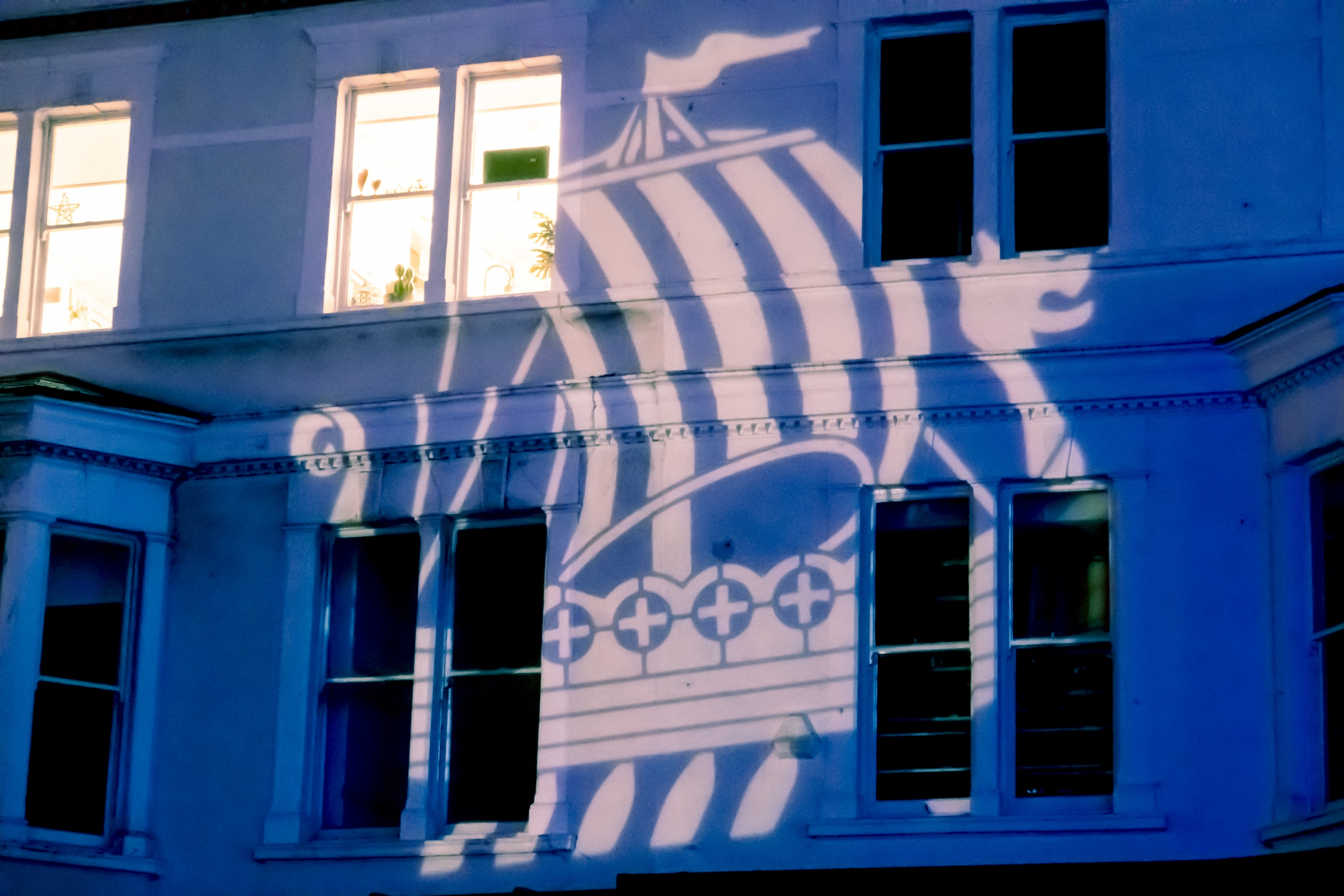 Coloured outdoor lighting and gobo projection at the Llandudno Winter Light / Golau Gaeaf event, in North Wales. A building on Mostyn Street is illuminated in blue with a white gobo of a Viking ship.