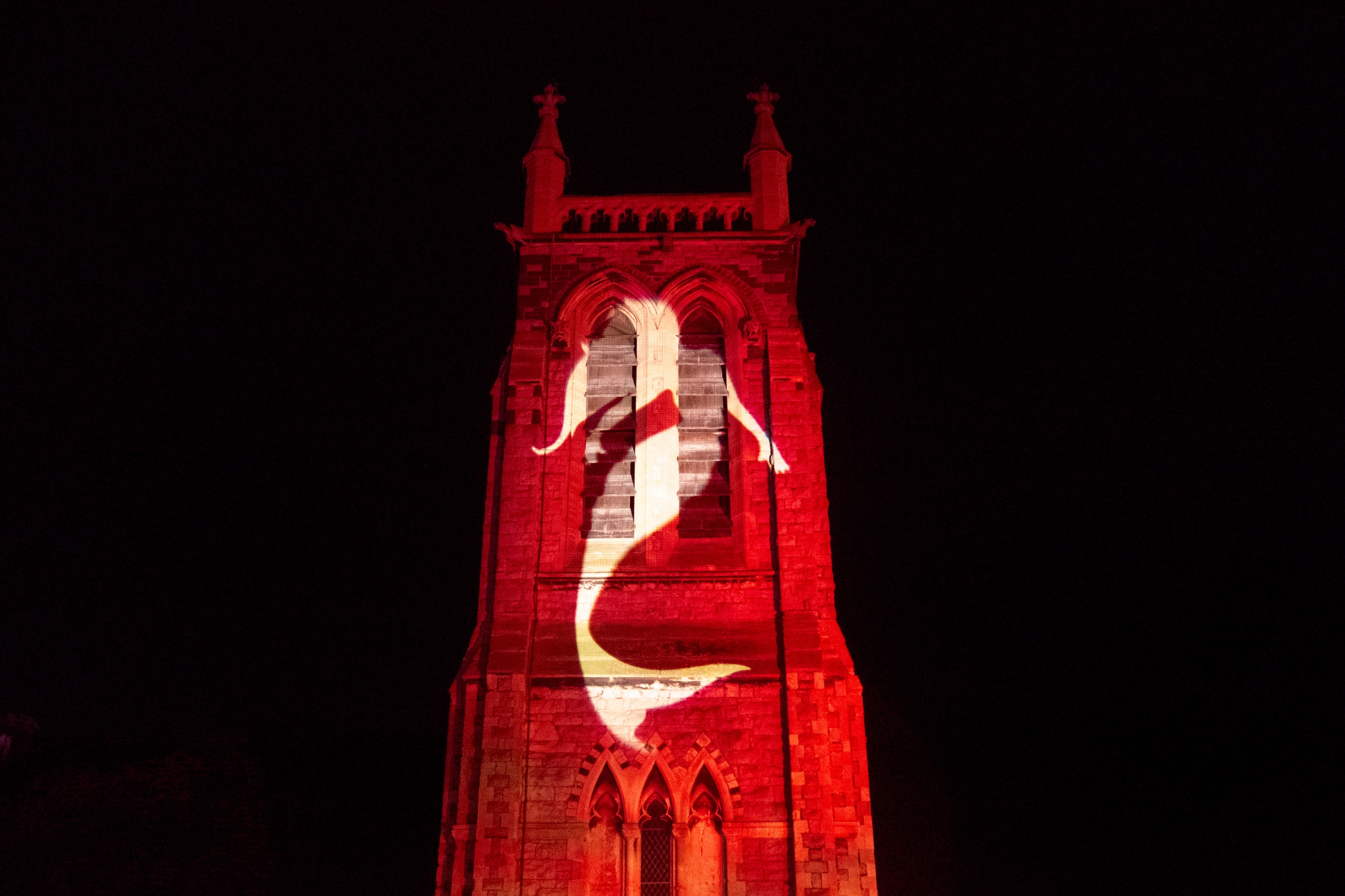 Coloured outdoor lighting and gobo projection at the Llandudno Winter Light / Golau Gaeaf event, in North Wales. The tower of Holy Trinity Church on Mostyn Street is illuminated in red with a white gobo of a mermaid.