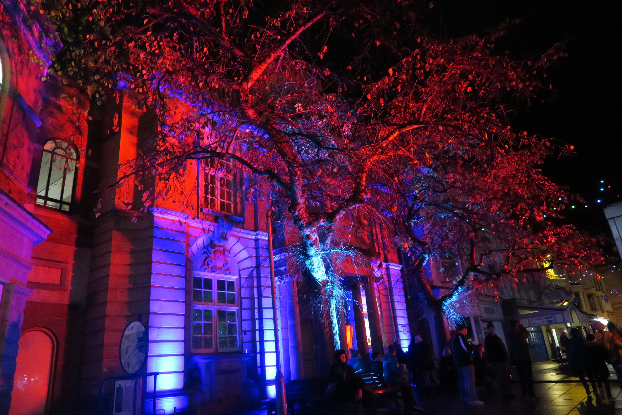 Coloured outdoor lighting at the Llandudno Winter Light / Golau Gaeaf event, in North Wales. The Library on Mostyn Steet is illuminated in red and blue, by weatherproof LED flood lighting.