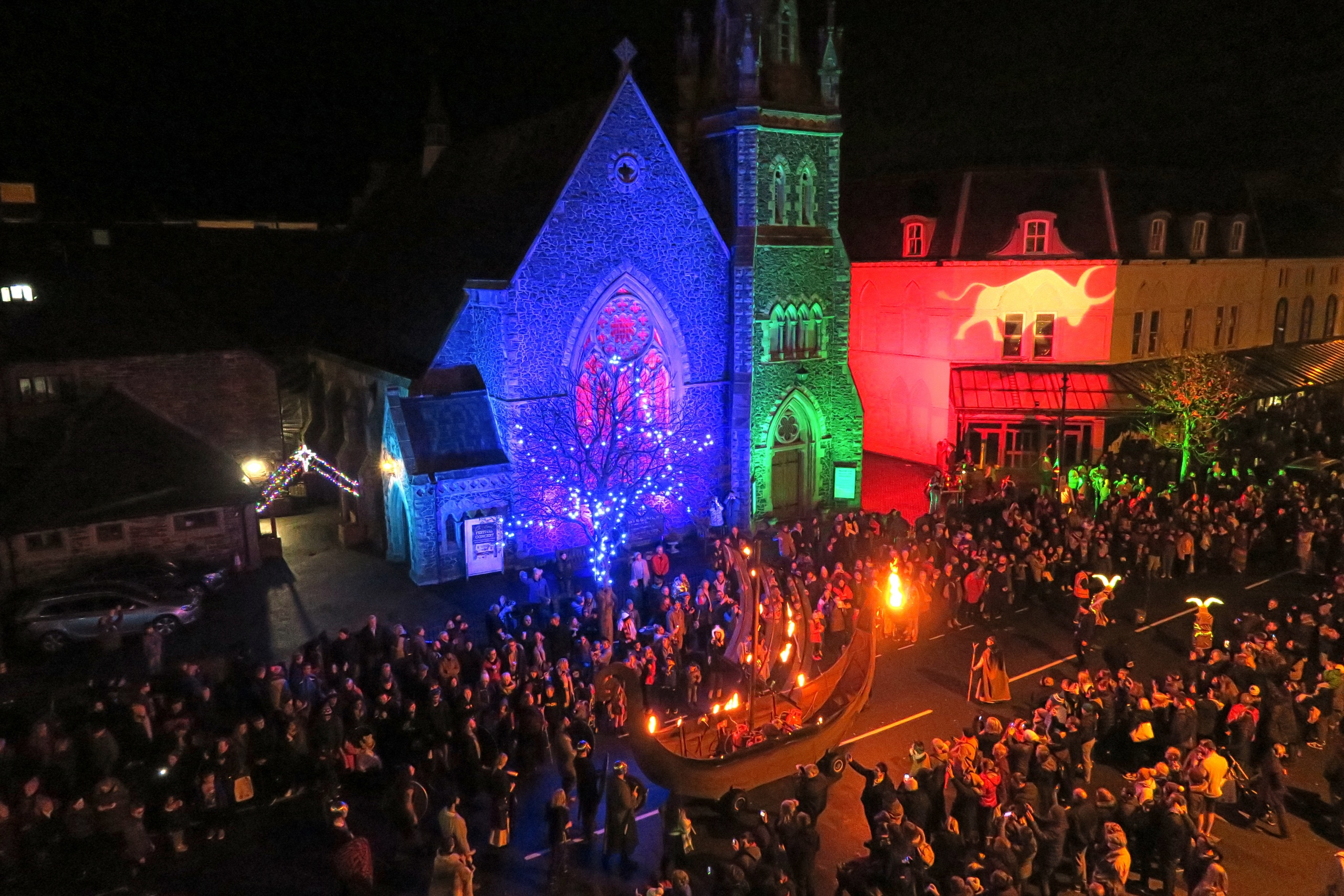 Coloured outdoor lighting at the Llandudno Winter Light / Golau Gaeaf event, in North Wales. To complement the parade, St Johns Church on Mostyn Steet and adjacent buildings were illuminated with weatherproof LED flood lighting & gobo projections including a giant ox.