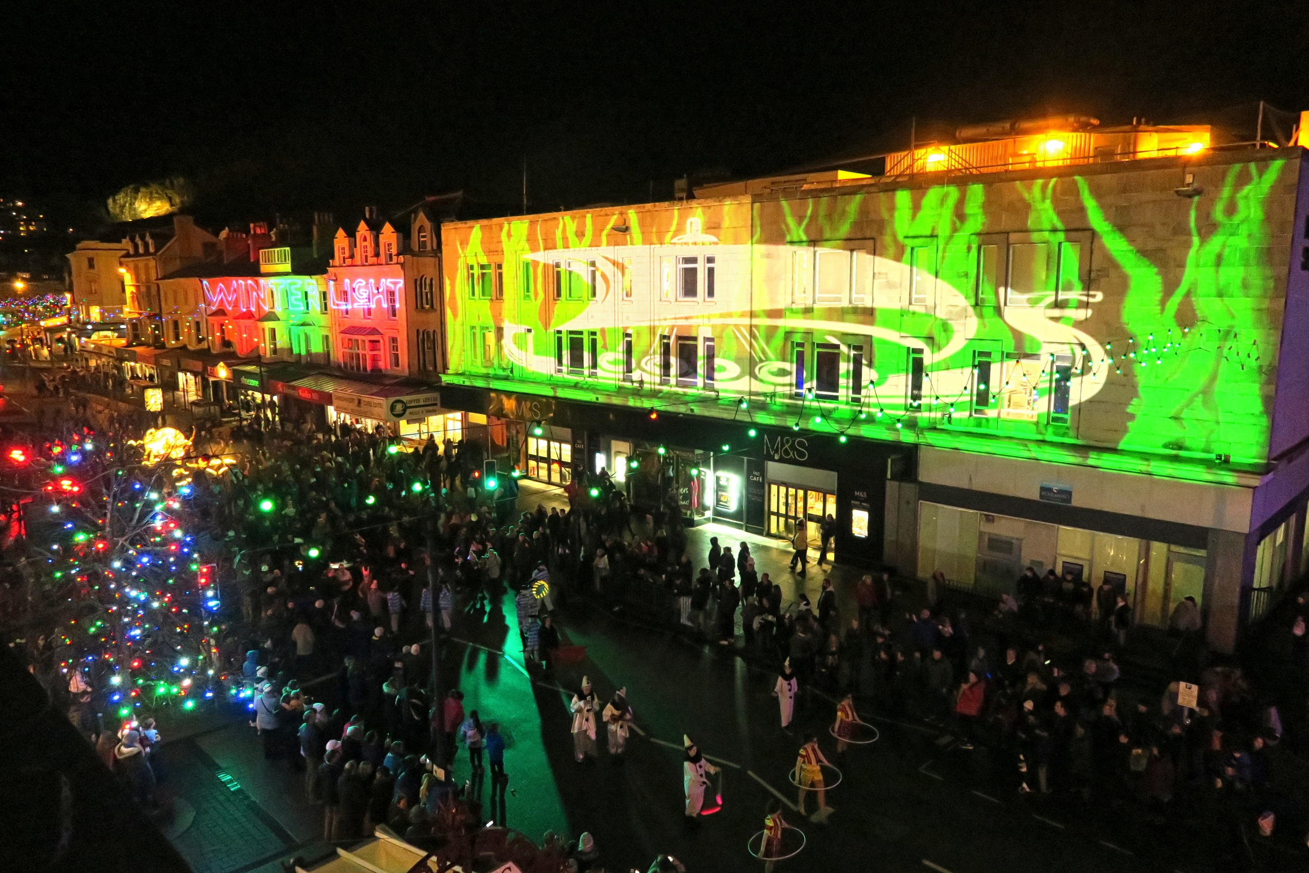 Outdoor projection mapping on to buildings at the Llandudno Winter Light / Golau Gaeaf event, in North Wales. To complement the parade, the wall above Marks & Spencer on Mostyn Street is illuminated by edge blended projectors, from the Library and Victoria Shopping Centre opposite.