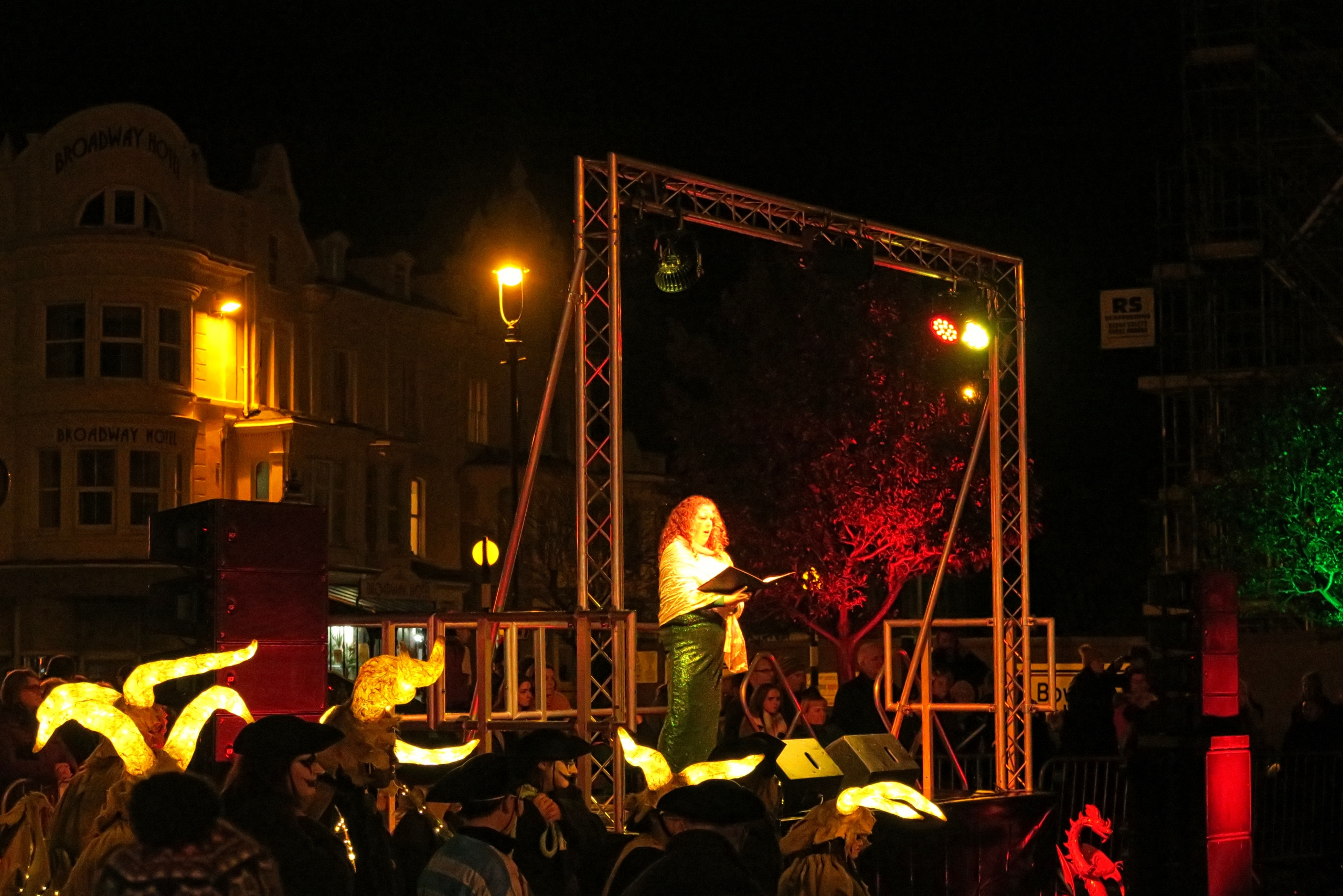 Coloured outdoor lighting at the Llandudno Winter Light / Golau Gaeaf event, in North Wales. Parade finale with opera singer, on outdoor stage. Stage illuminated with overhead truss in red, yellow and warm white.