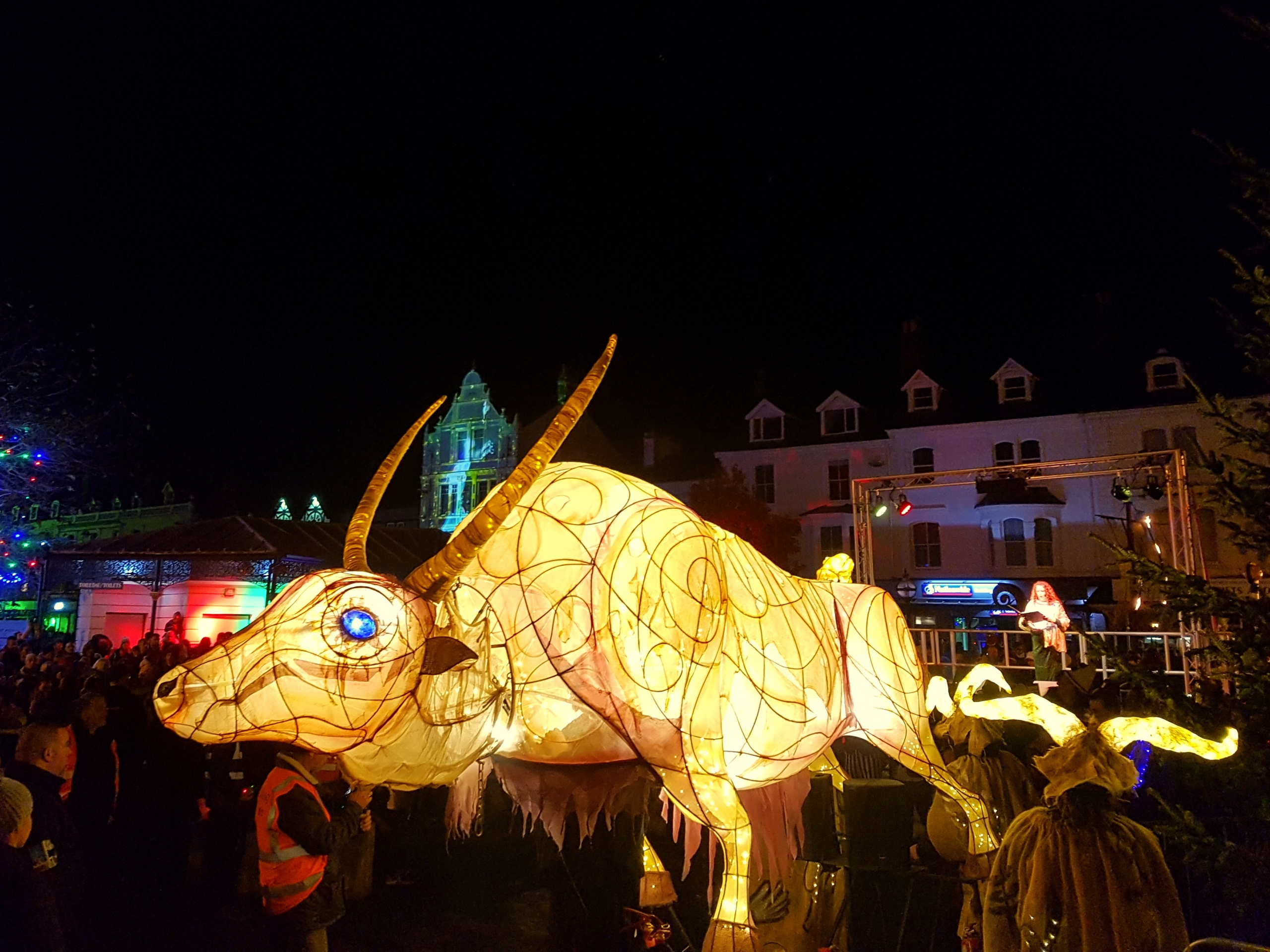 oloured outdoor lighting at the Llandudno Winter Light / Golau Gaeaf event, in North Wales. Illuminated horned ox at parade finale with opera singer, on outdoor stage. Illuminated toilets in background.