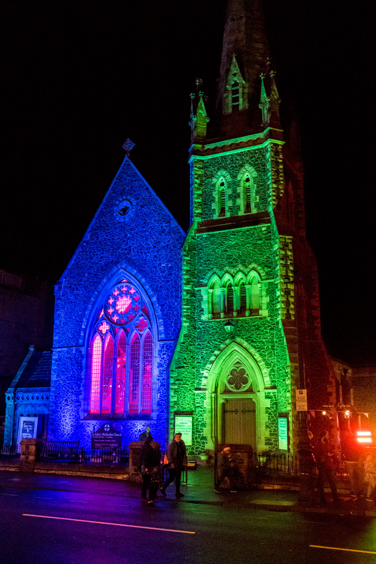 Coloured outdoor lighting at the Llandudno Winter Light / Golau Gaeaf event, in North Wales. St Johns Church on Mostyn Street is illuminated with blue and green weatherproof LED up lighting, with red lighting through the stained glass window.