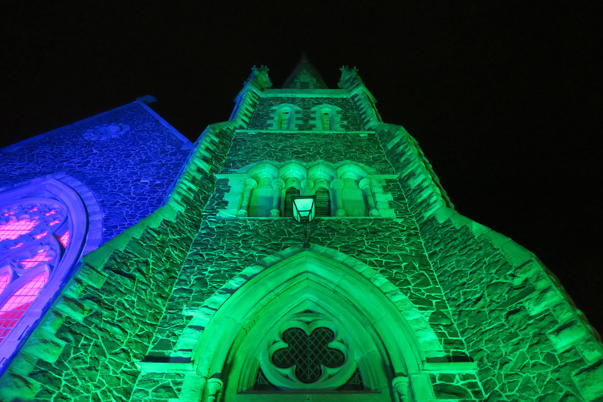 Coloured outdoor lighting at the Llandudno Winter Light / Golau Gaeaf event, in North Wales. St Johns Church on Mostyn Street is illuminated in green and blue with weatherproof LED up lighting,