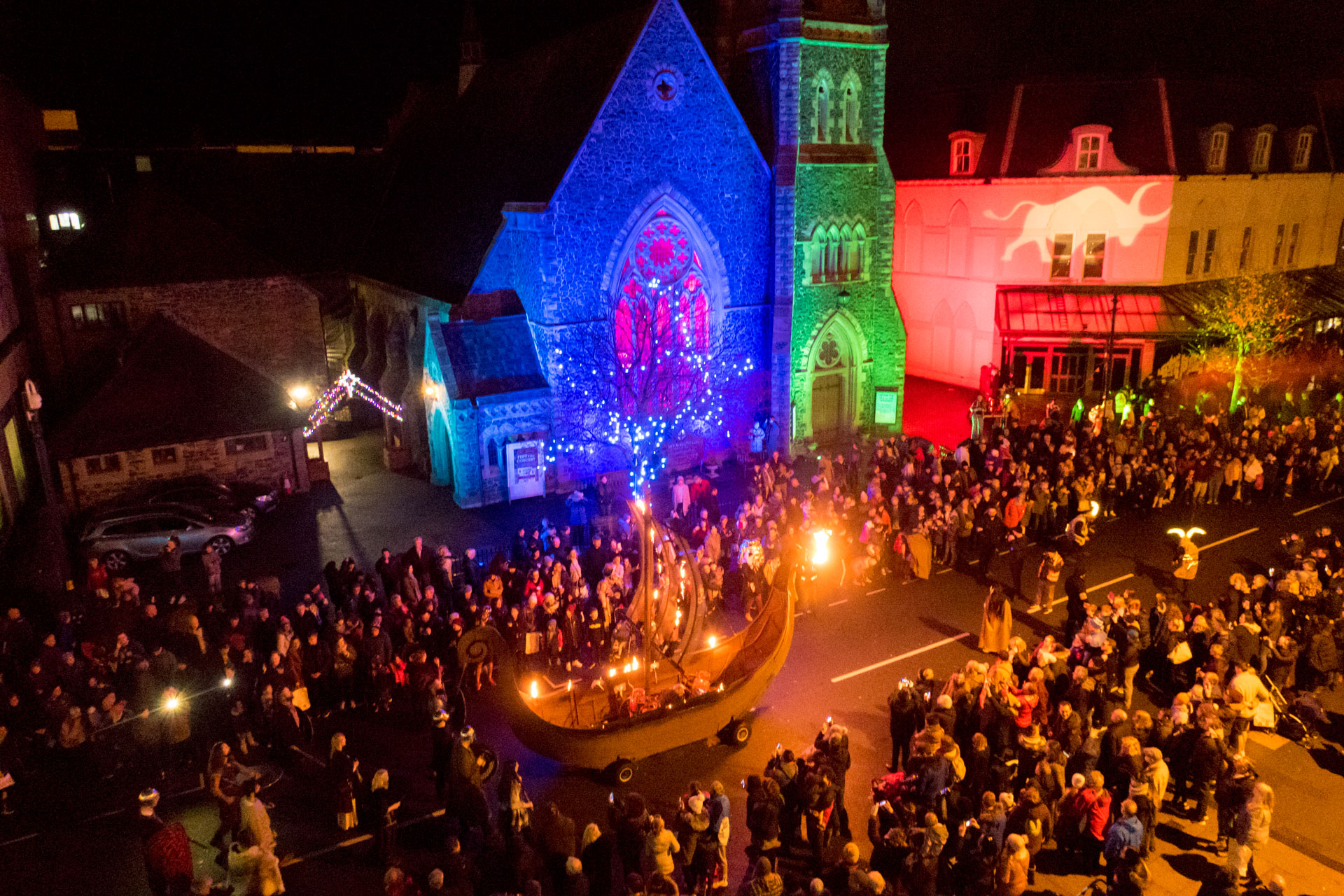 Coloured outdoor lighting at the Llandudno Winter Light / Golau Gaeaf event, in North Wales. To complement the parade, St Johns Church on Mostyn Steet and adjacent buildings were illuminated in blue, green and red with weatherproof LED flood lighting & gobo projections including a giant ox.