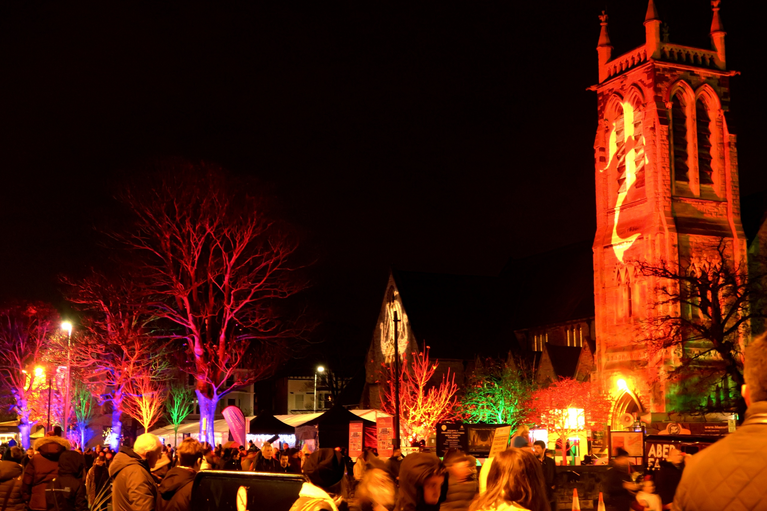 Coloured outdoor lighting and gobo projection at the Llandudno Winter Light / Golau Gaeaf event, in North Wales. The tower of Holy Trinity Church on Mostyn Street is illuminated in red with a white gobo of a mermaid. The trees are lit in magenta and blue.