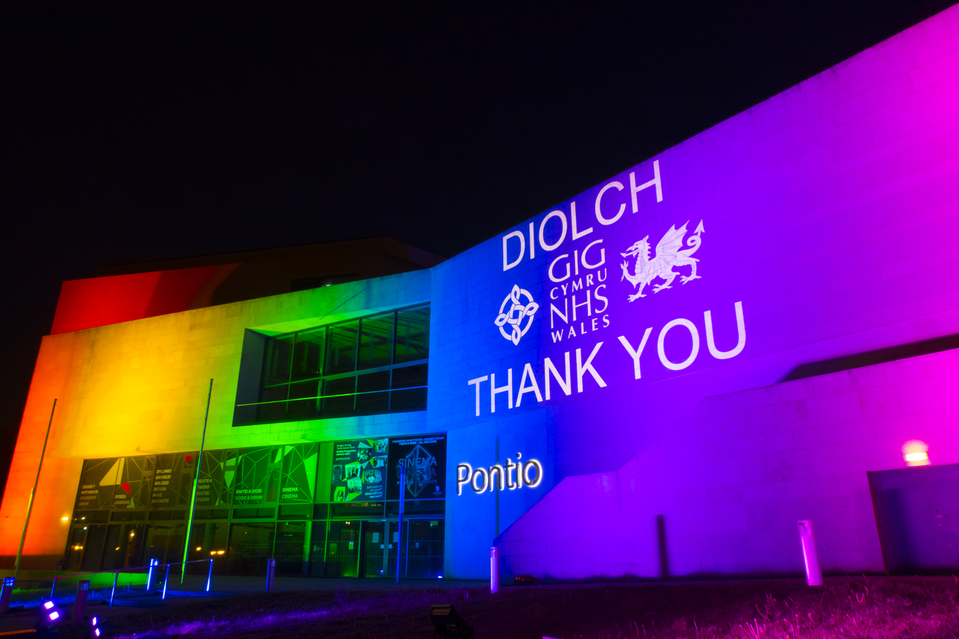 Outdoor projection & lighting on Pontio Theatre, Bangor, to say thank you to the NHS, rainbow coloured lighting, white logo.