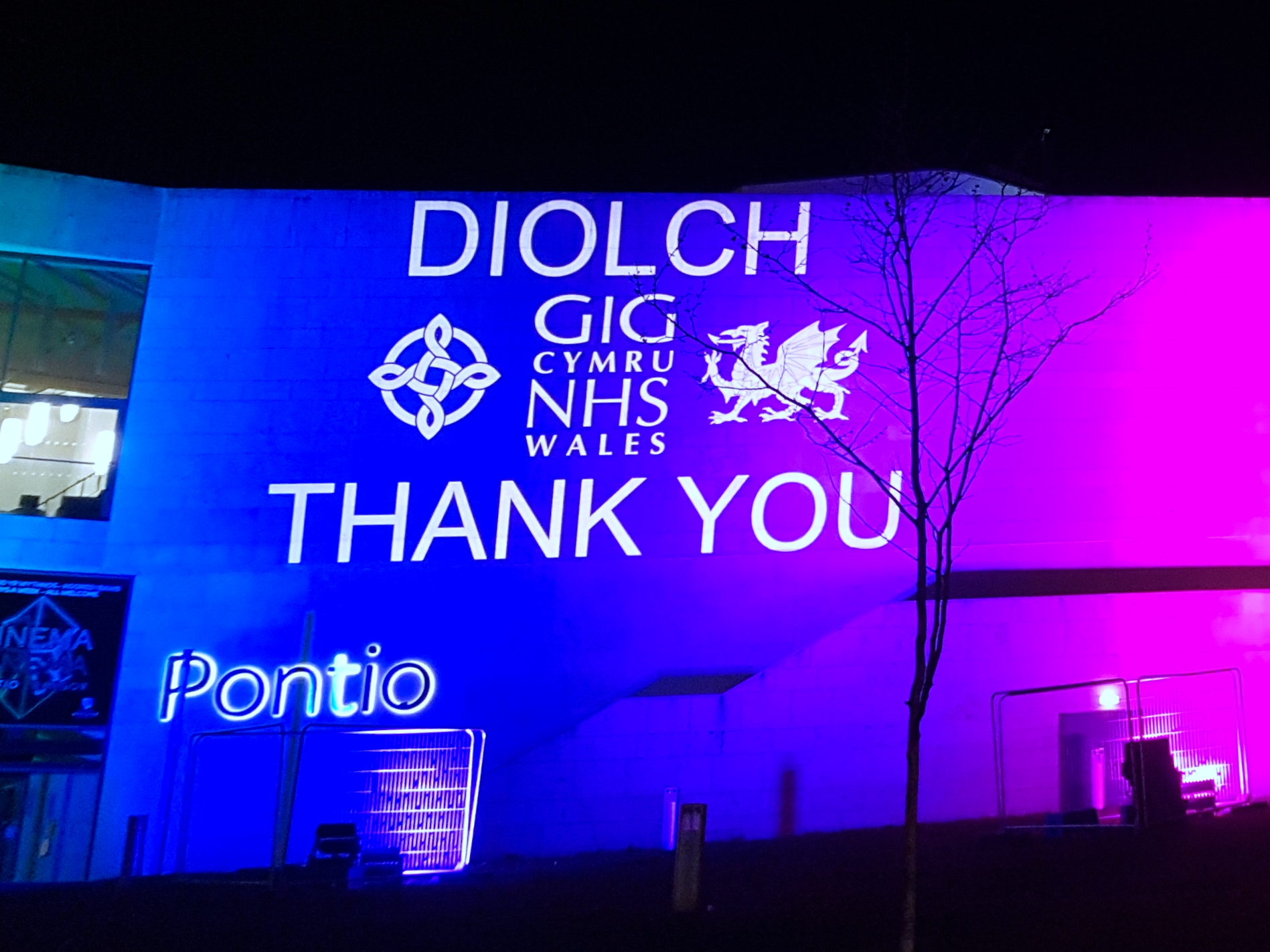 Outdoor projection & lighting on Pontio Theatre, Bangor, to say thank you to the NHS, blue lighting, white logo.